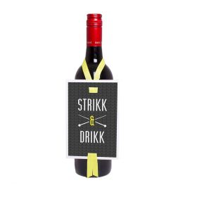 """Vinkort med teksten """"strikk og drikk"""" i fargene hvit og sort med hvit skrift og gule detaljer. Kortet har også to strikkepinner på hver sin side av """"og"""" ordet og gult sløyfebånd som går rundt flaskens hals og kan regulere høyden til koretet rundt flasken"""