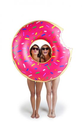 stor donut formet badering med rosa glasur på toppen med fargerik strøssel over. men vent, det er noen som har tatt et bitt av den, men det er heldigvis ikke så stort