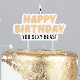 """gullfarget skrift """"happy birthday"""" og sortfarget skrift under """"you sexy beast"""" med hvit bakgrunn og ett lys du kan tenne på på toppen av kakelyset"""