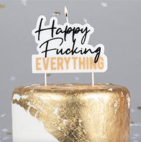 happy fucking er skrevet i sort løkkeskrift forså at everything står i gullfarget blokkbokstaver under. er et lys til å tenne på på toppen av kakelyset