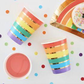 pappkrus i med metallisk gull som bakgrunn og sirkler rundt glasset i fargene rød, orrange, gul, grønn, blå og lilla på rekke og hver sin sirkel nedover kruset